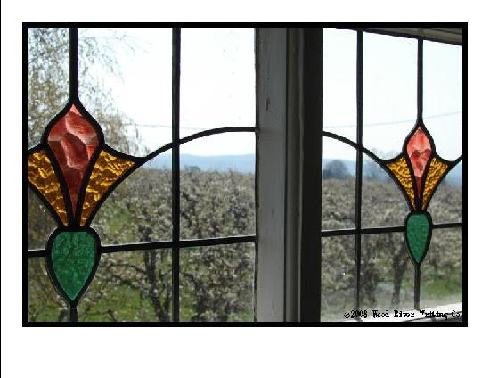 Apple Country Bed and Breakfast: Stained Glass Windows in Upstairs Bath, Pear Orchard in Background