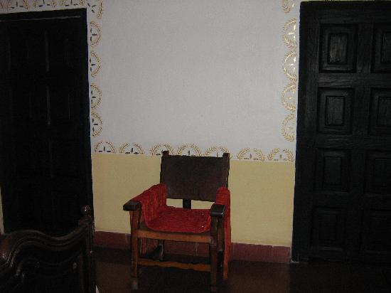 Hacienda Vista Hermosa: Antique leather chair flaked by bathroom and dressing room doors.