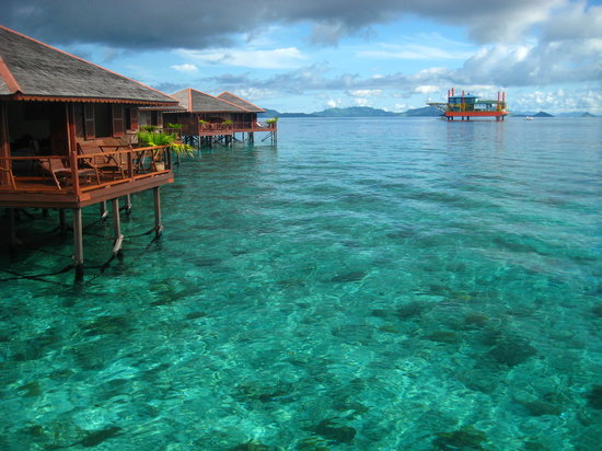 Pulau Sipadan, Malasia: SWV water bungalows with a repurposed oil rig in the background