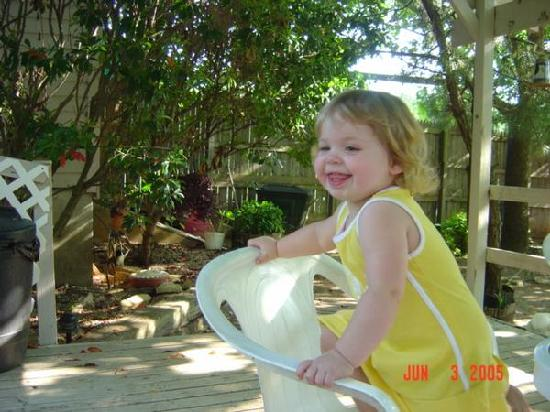 Secret Garden Cottages: My daughter sitting on the deck.  You can see a small portion of the garden in the background.