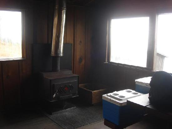 Steep Ravine Cabins: Inside the cabin, the table and stove area, with big windows looking out to the water