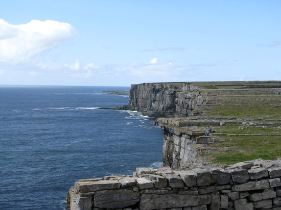 Inishmore, Irlande : Canadian tourist playing the penny whistle on the cliff