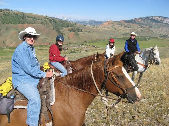 Red Rock Ranch: Family riding fun in the hills above the ranch - Grand Tetons in the background and ranch spreab