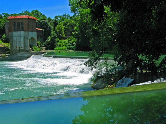 Seguin, TX: The green lush water flows over the dam.