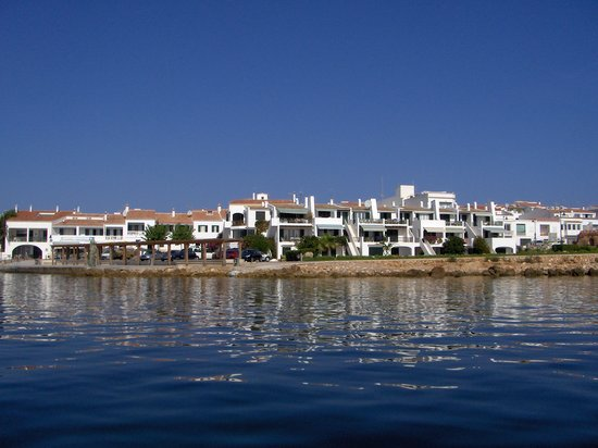Fornells, Spain: C'an Digus and Sa Nansa from a boat just offshore., with a private apartment block in the foregr