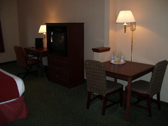 Auburn Place Hotels and Suites: Table with two chairs, television cabinet, and desk with office-type chair