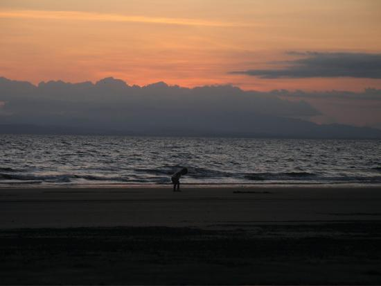Cabinas Los Cocos: A local boy plays in the sand at sunset.