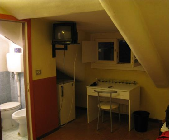 "Artua & Solferino: Room (Economy ""mansardata"") showing bathroom, window, desk, fridge."