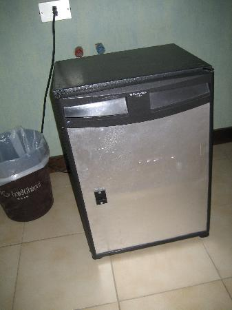 old, noisy refrigerator with pipes behind