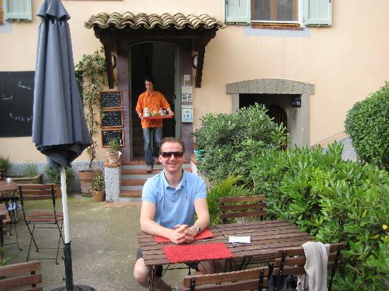 The Frogs' House: Eingang zum Frog House mit Benoit im Hintergrund ein Tablett mit hausgemachter Marmelade tragend