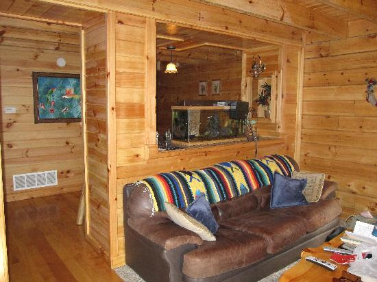 Buckeye Cabins: Living room couch with dining area beyond aquarium