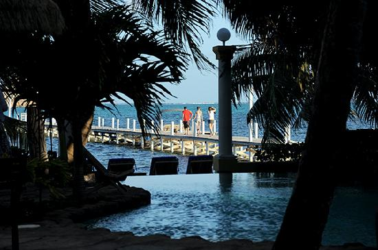 Pelican Reef Villas Resort: View from our room across pool to sea, pier, palms...
