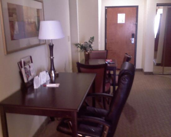 Comfort Suites East: Work area and eating table, Door leading to hallway in background.
