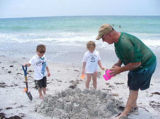 Tommy's on the Beach: kids making a sand castle.  Beautiful blue water in the back ground