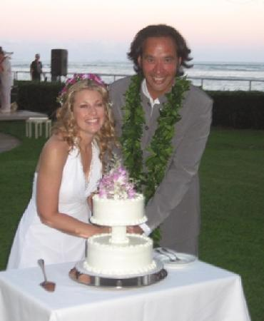 cutting our wedding cake on the lawn of Orchids