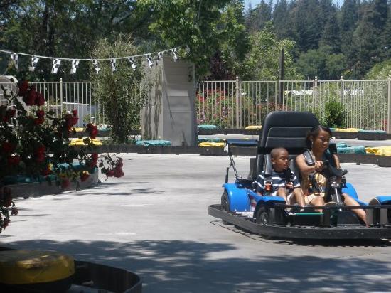 Arrowhead Pine Rose Cabins: Kids driving cars at the local Fun Spot