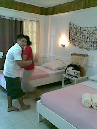Mito's Place Boracay: Our room. A doubles bed and a singles bed. Didn't mind the pink sheets. That my friend walking p