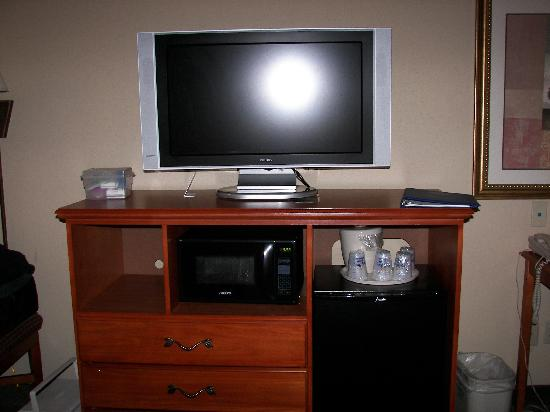 Holiday Inn Express & Suites Parkersburg - Mineral Wells: Flat screen TV in dresser with microwave and fridge