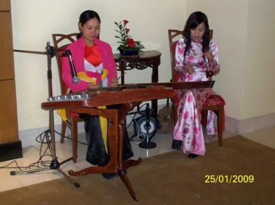 ฮานอย, เวียดนาม: 右邊的樂師所用的是「獨弦琴」,只有一條線,全靠左邊的棍的移動來轉變音色
