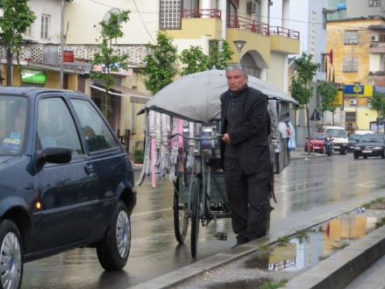ติรานา, แอลเบเนีย: Амбулантен търговец по улицата, водеща към Дурас.