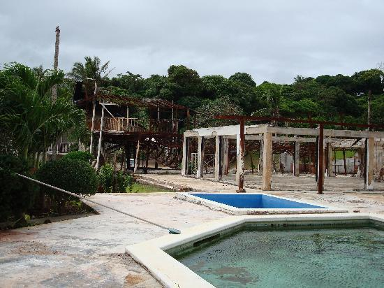 The Paradise International Hotel : Pool with fire damaged area in background.