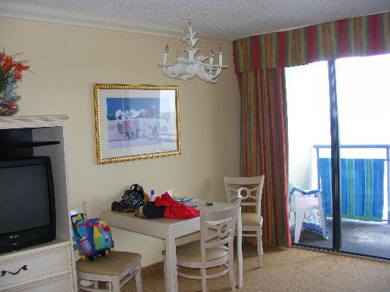 Coral Beach Resort & Suites: Living room.  Has a sofa, wall mounted bed, and a balcony overlooking the ocean (not shown)