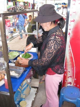 Vientiane, Laos: Sexy auntie preparing my baguette with moo moo cheese!!! I was salivating while she took her tim