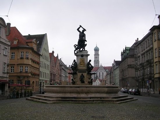 Augsburg, Alemanha: The Hercules Fountain with the former Benedictine abbey church of St. Ulrich and St. Afra on Max
