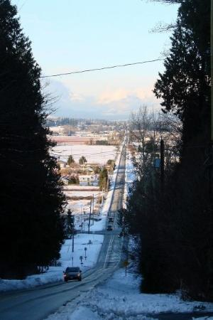 Surrey, Kanada: Looking north along a major road. The mountains in the distance are behind the main part of Vanc