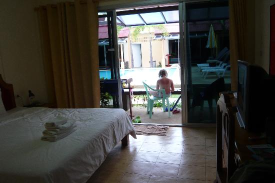 Rico's Bungalows: part of the room with the bed, tv and outside view