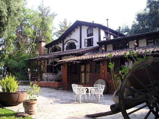 Hacienda Don Juan Hotel: Frente del hotel, tras una barda