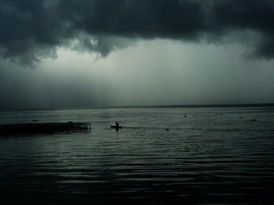 Bukittinggi, Indonesia: The fisherman canoing through the lake towards the heavy rain.