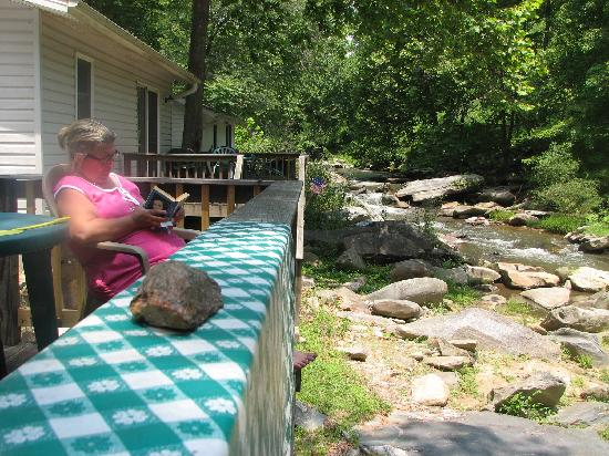 River View Cabins: Photo of My Wife Sitting on the Back Porch of The Sunflower House Cabin