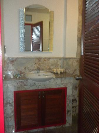 La Paillote Guesthouse : bathroom sink. toilet is behind the door and marble shower is just behind that