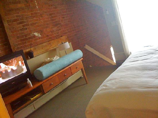 Mill Street Inn: 2nd level (bedroom), TV on the left, stairs on the background, glass sliding door to the private