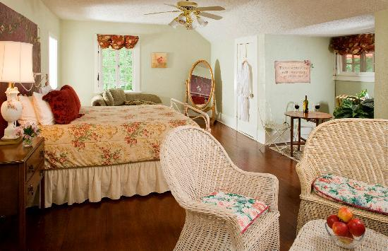 Hilltop Manor Bed & Breakfast: Rose Suite - A feminine room with white wicker and flowers plus a Jacuzzi tub combined with the