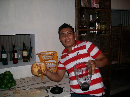 Livingston, Guatemala: A barman making a Coco Loco drink in restaurant opposite