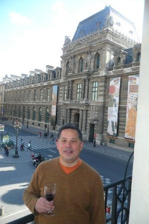 Ken enjoying a glass of wine from our room balcony at the L'Hotel du Louvre.  That's the Louvre