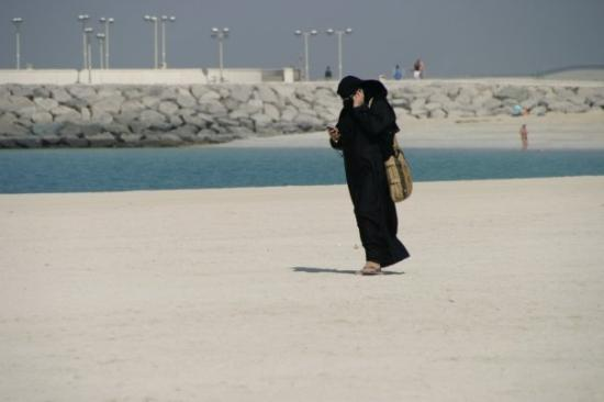 Jumeirah Public Beach: Veiled woman walking along Persian Gulf on Dubai Jumeirah Beach