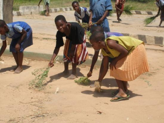 Harare, Zimbábue: School girls sweeping the school yard with torn vegetation. This is an afterschool project.