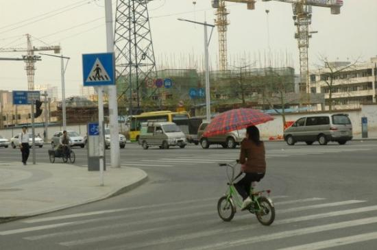 Girl with umbrella on bicycle in Dongguan, China.