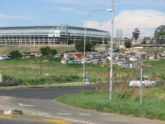 Johannesburg, Sør-Afrika: The new soccer stadium in Soweto...with a makeshift shack village in the foreground.  Most who l