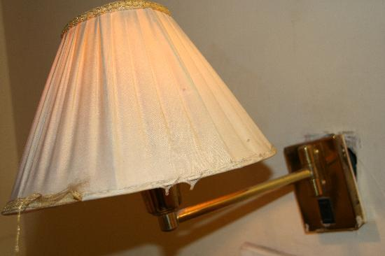Hotel Perfect: dirty broken bedside lamp hanging off the wall
