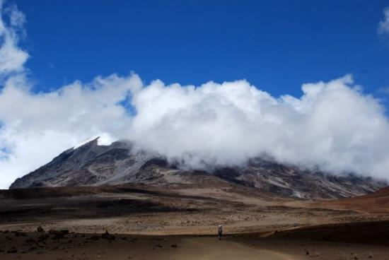 Kilimanjaro National Park, Tanzania: Moutain, clouds, and a porter carrying more than his own weight...