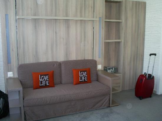 Aparthotel Adagio Basel City: wooden panel pulls down into a full bed, sofa tucks under.