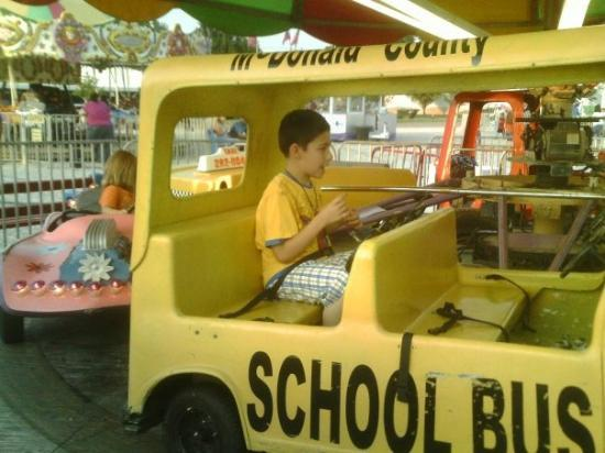 Saint James, MO: Austin loved the cars that went in a circle. Here he is driving a school bus.
