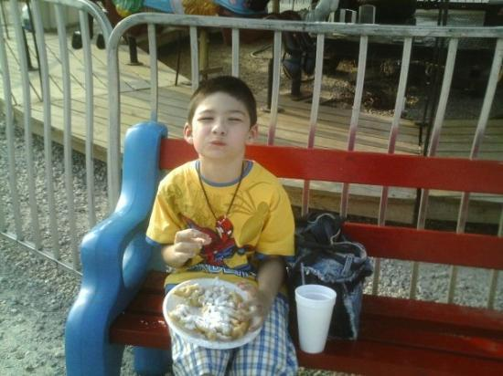 Saint James, MO: Austin takes a break from the rides to eat a funnel cake.