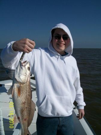 Buras, LA: Joey and the first catch of the day, a 4 lb redfish. It was windy and in the 50's, but clear an