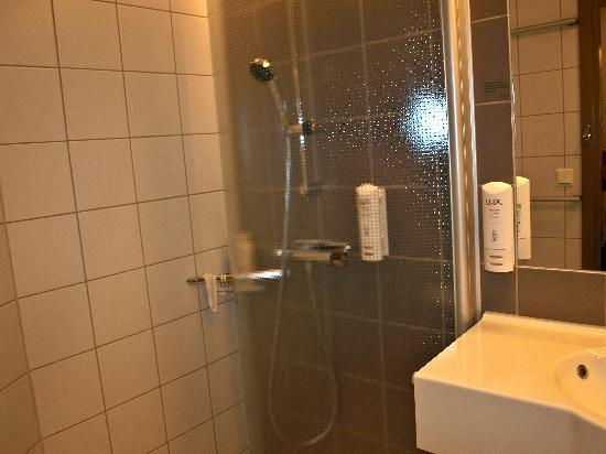 Scandic Alvik: bathroom - see the movable shower door swung back against the taps