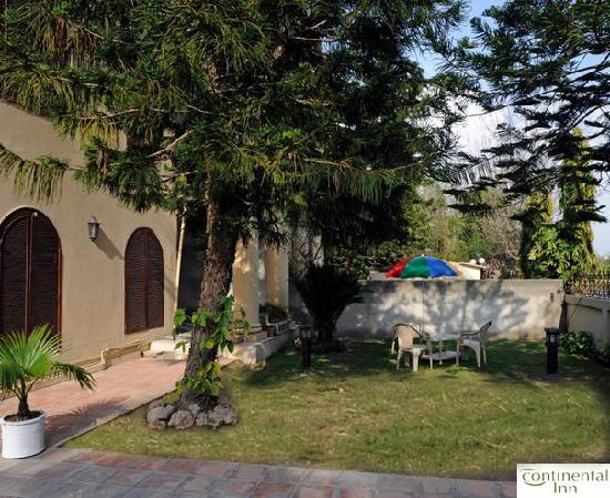 Continental Inn Islamabad : Front Lawn with Chairs, Table & Umbrella